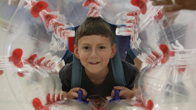 Eight-year-old Logan Jones climbs into a Bump N Play plastic bubble during his birthday Sunday at the Police Athletic League Center in Hockessin.