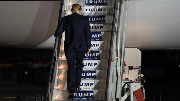 Donald Trump boards his plane following a rally on