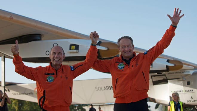 Pilots Bertrand Piccard, left, and Andre Borschberg, right, celebrate the landing of a solar-powered plane at San Pablo airport in Seville, Spain on Thursday, June 23, 2016. An experimental solar-powered airplane Thursday completed an unprecedented three-day flight across the Atlantic in the latest leg of its globe-circling voyage.
