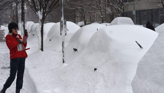 AFP_7C4RQ.jpg A woman takes pictures of snow covered cars in Washington, DC January 23, 2016.A deadly blizzard with bone-chilling winds and potentially record-breaking snowfall slammed the eastern US on Saturday, as officials urged millions in the storm's path to seek shelter -- warning the worst is yet to come. US news reports said at least eight people had died by late Friday from causes related to the monster snowstorm, which is expected to last until early Sunday.  / AFP / Mladen ANTONOVMLADEN ANTONOV/AFP/Getty Images