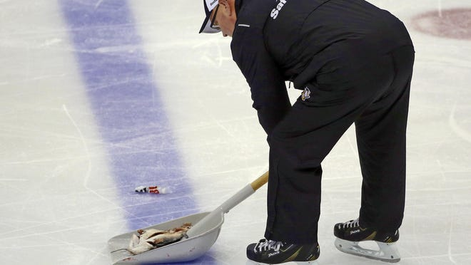 """An ice worker removes a fish during the second period of Game 1 of the NHL hockey Stanley Cup Finals between the Pittsburgh Penguins and Nashville Predators on Monday, May 29, 2017, at PPG Paints Arena in Pittsburgh. Authorities said Jacob Waddell, of Nolensville, Tenn., is facing charges after allegedly throwing a dead catfish onto the ice during the hockey game, including misdemeanor counts of possessing instruments of crime and disrupting meetings or processions, as well as a summary count of disorderly conduct. The Tennessee Bureau of Investigation commented on social media that investigators had never seen an """"instrument of crime"""" like that. (AP Photo/Gene J. Puskar)"""