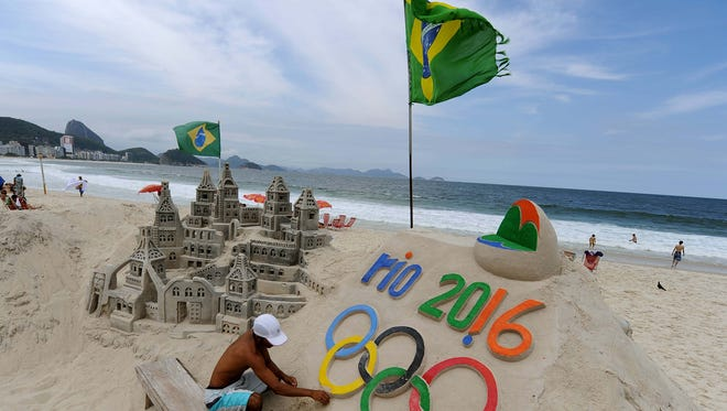Sand sculptor Rogean Rodrigues puts the finishing touches on the Olympic Rings — near an elaborate castle on Copacabana beach.