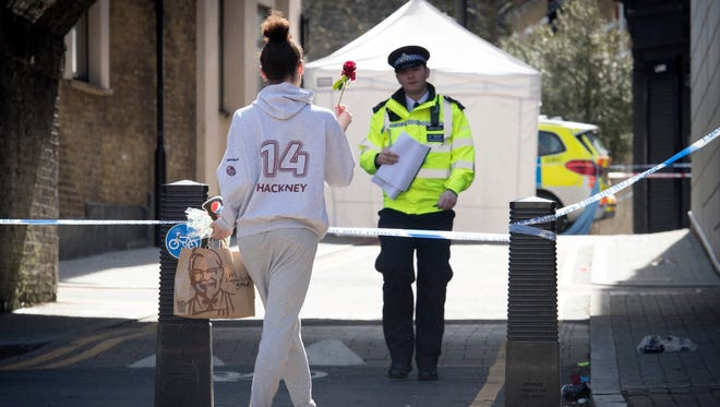 A woman carries a flower to a crime scene in Link Street, Hackney, east London, Thursday April 5, 2018.