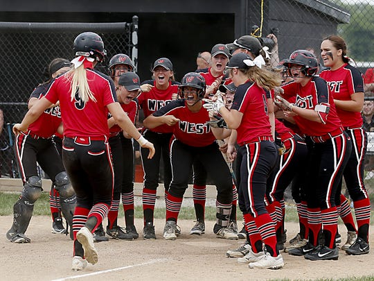 Alyssa Triner (9) is greeted at home plate by her Lakota West teammates after Triner hit a two-run homerun off Lebanon in their Division I regional softball final at Centerville Saturday, May 26, 2018.
