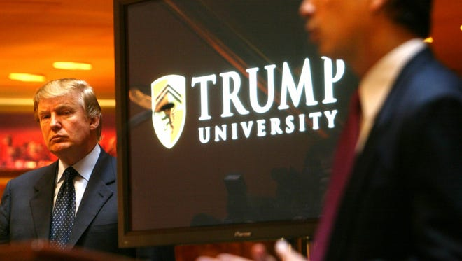 Real estate mogul and TV star Donald Trump, left, listens as Michael Sexton introduces him to announce the establishment of Trump University at a press conference in New York, Monday May 23, 2005. S