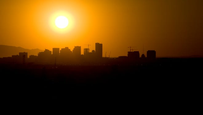 The sun sinks behind the downtown Phoenix skyline in June 2007.