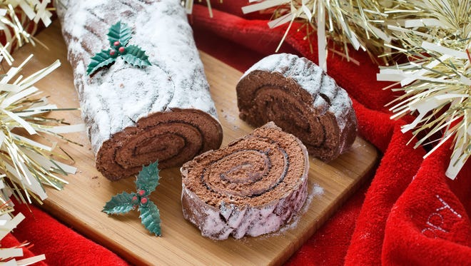 """Buche De Noel, France: Once an actual log burning in a fireplace on Christmas Eve -- to celebrate the days starting to get longer -- the buche de noel has been transformed over centuries into an edible yuletide cake. Instead of wood and bark, the buche de noel (or """"yule log"""") consists of a thin genoise sponge that's spread with a sweet filling, rolled into a roulade, and piped with buttercream. Score marks are made with a fork to resemble tree bark, and decorations such as meringue mushrooms and marzipan holly evoke the forest floor."""