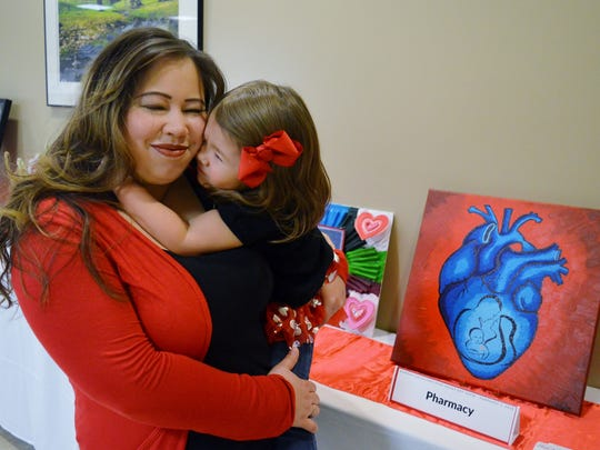 Miya Hawley hugs her mother Nichole Wilcox- Hawley at the Show us Your Heart art show at Kaweah Delta Medical Center. Miya was born with a rare heart defect where a portion of the aorta blood vessel is narrowed.