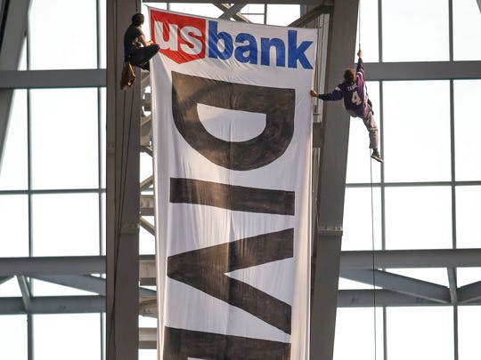 Two protestors hang from the rafters with a banner