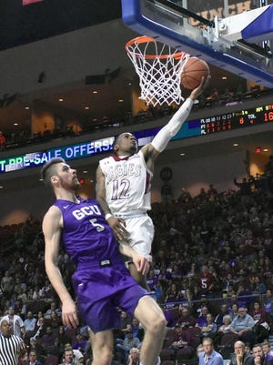 New Mexico State's AJ Harris goes in for a easy layup against Grand Canyon University's Matt Jackson on Saturday night during the WAC Tournament championship game at Orleans Arena in Las Vegas, Nevada.