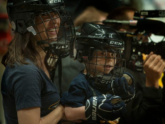 Ashley Daniel holds her son Caleb, 5, on the Preds