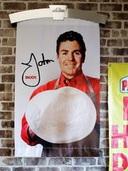 In this Dec. 21, 2017, file photo shows signs, including one featuring Papa John's founder John Schnatter, at a Papa John's pizza store in Quincy, Mass. Papa John's plans to pull Schnatter's image from marketing materials after reports he used a racial slur. Schnatter apologized Wednesday, July 11, 2018, and said he would resign as chairman after Forbes reported that he used the slur during a media training session. Schnatter had stepped down as CEO last year after criticizing NFL protests.
