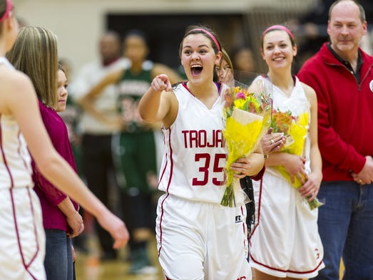 Center Grove High School senior Madi Kolthoff (35) reacts to a teammate as she and fellow senior Bobbie Clayton (20) were recognized during pre-game activities of girls varsity basketball action Friday, Jan. 31, 2014, at Center Grove High School.
