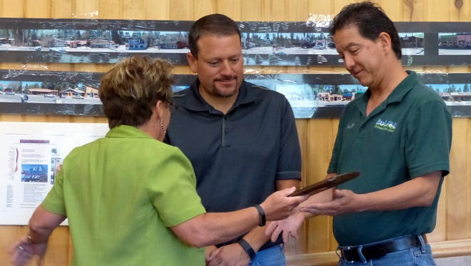 Manny Cordova, right, receives a plaque from Ruidoso Village Manager Debi Lee marking his retirement. At center is Rodney Griego, director of Parks and Recreation.