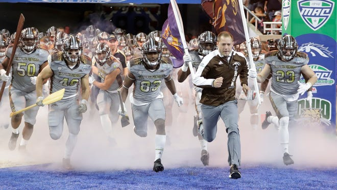 Western Michigan head coach P.J. Fleck runs onto the field with his team before the Mid-American Conference championship NCAA college football game against Ohio, Friday, Dec. 2, 2016, in Detroit.
