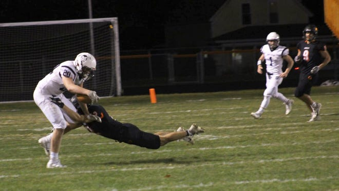 Sault High's Callen Campbell (20) hauls in a catch from Jakob Davie (1) during a playoff game at Ludington Friday night. Cambell and Davie also combined on the game-winning, 5-yard touchdown pass on the last play, giving the Blue Devils a 22-16 victory.