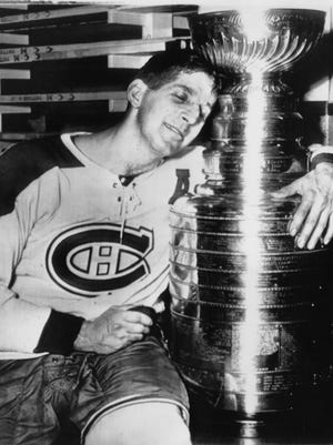 Montreal Canadiens center Elmer Lach hugs the Stanley Cup in the dressing room at the Montreal Forum after scoring the game-winning goal in overtime in Game 5 of the Stanley Cup Final against the Boston Bruins in 1953.