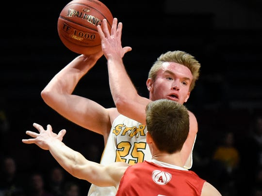 Sauk Rapids' Anthony Massman makes a pass over Austin's Tate Hebrink during the first half Wednesday, March 21, in the first round of the state Class 3A boys basketball tournament at Williams Arena in Minneapolis.
