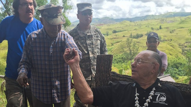 """Uncle"" Buck Cruz, 88, 3rd Marines, second from left, exchanges a firm handshake with Gene Bell, 89, 3rd Marines and Guam Liberator, on the Merizo hillside at Faha on July 15, during a memorial held for the victims and survivors of the 1944 Faha Massacre."