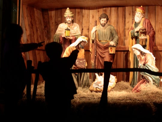 Children look over a Nativity scene during Downtown