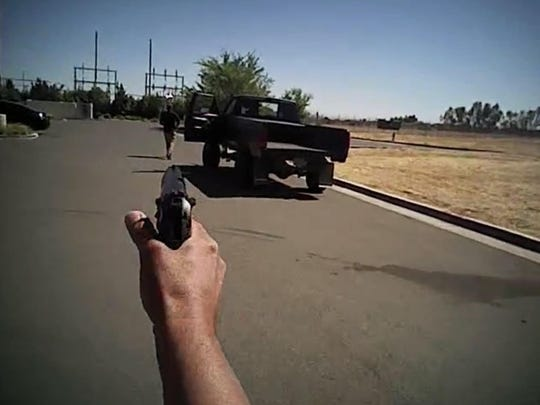 In this image made from a June 25, 2016, police body-camera video released by Fresno Police Department, a police officer points a gun towards Dylan Noble showing his back next to his pickup truck as the officer moves towards Noble walking away from the officer in Fresno. Fresno police on Wednesday, July 13, released body-camera video of officers fatally shooting Noble, 19-year-old man who ignored repeated commands to stand still and show his hands.