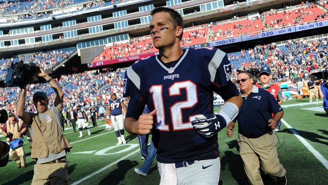 New England Patriots quarterback Tom Brady (12) walks off the field after defeating the Jacksonville Jaguars 51-17 at Gillette Stadium.