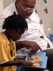 "The Rev. Angus Thompson, shown reading to a child in this file photo, will speak during ""The Black Migration Gospel Service"" at the church at 1420 Borton St. on Feb. 24."
