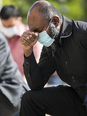 Pastor Nice Mualis of the Angolan Association bows his head in a prayer for healing during a vigil at Brockton City Hall Plaza on Monday evening, June 1, 2020.