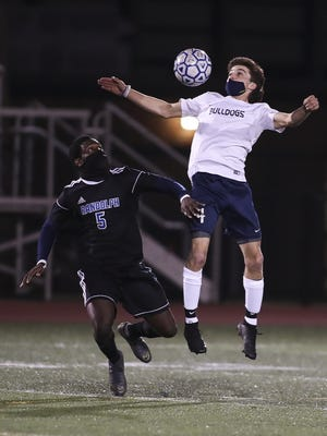 Rockland's Nick Blonde bodies the ball as he's pressured by Randolph's Angelot Jerome in the second round of the South Shore League Cup game at Randolph High School on Monday, Nov. 9, 2020.