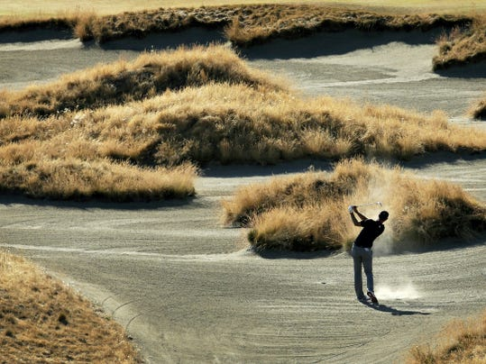 Dustin Johnson hits out of the bunker on the 14th hole during the second round of the U.S. Open golf tournament at Chambers Bay on Friday in University Place, Wash.