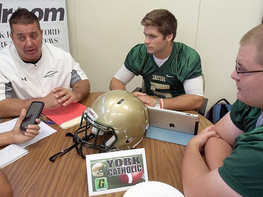 York Catholic head coach Eric Depew and players Like Brennan, center, and Ryan Ratchford talk during York-Adams Football Media Day. The Fighting Irish are coming off a second-place finish in Division III.
