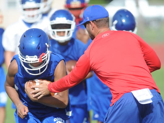Cooper assistant coach Cody Salyers, right, works a