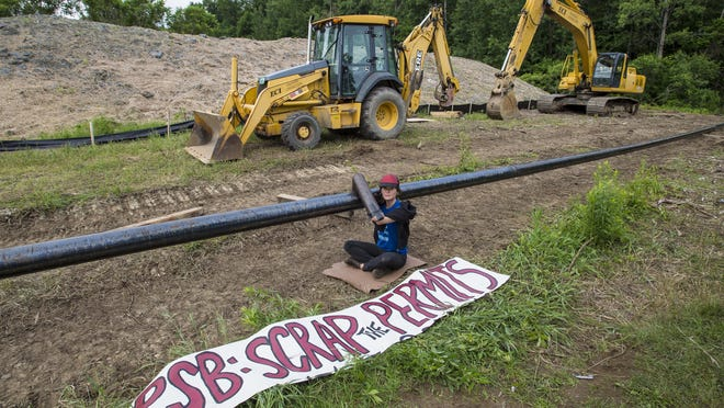 Johanna Anderson of Plainfield, a member of Rising Tide Vermont, is chained to a Vermont Gas pipeline under construction in Essex on June 18. Rising Tide opposes the new pipeline, which the group says will transport gas acquired by fracking.