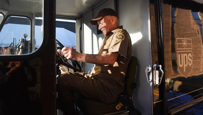 UPS driver Tom Camp inside a 1964 UPS delivery truck.