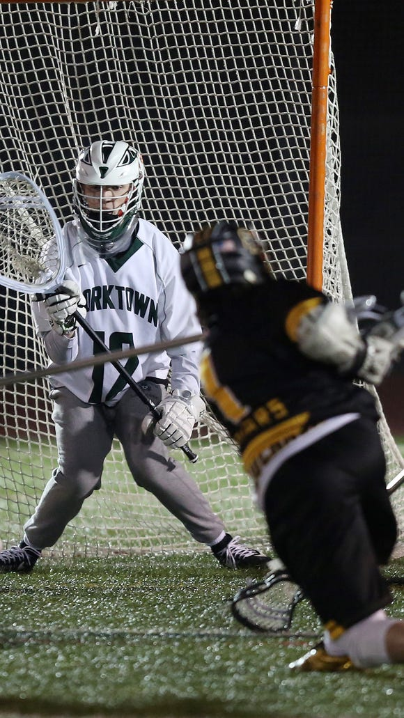 From left, Yorktown's Dan O'Meara (12) stops a shot against Saint Anthony's during boys lacrosse action at Yorktown High School March 27, 2018. Yorktown won the game 10-5.
