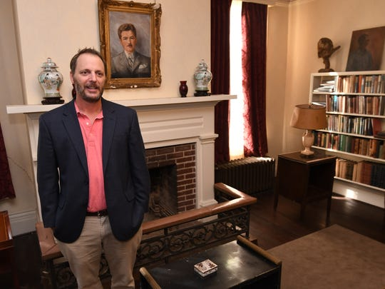 Rowan Oak curator Bill Griffith stands in front of a portrait of author William Faulkner at his Oxford home, which some claim is haunted.