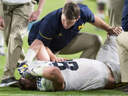 Michigan tight end Jake Butt is tended to after being