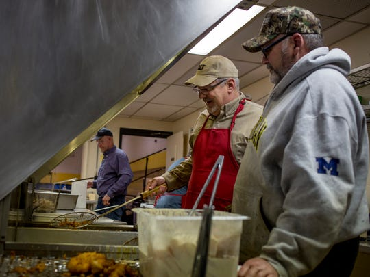Volunteers Tony Laudazio and Mark Ranshaw, both of St. Clair, chat as they work on frying fish during the weekly Lenten Fridays fish fry March 3, 2017 at St. Mary's in St. Clair. The two have volunteered for 12 and 17 years, respectively.