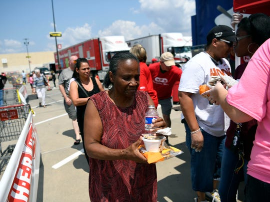 H.E.B. Grocery employees hand out hot lunches for those