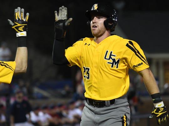 Southern Miss third baseman Luke Reynolds high-fives