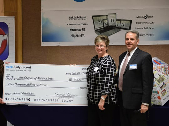 Vickie Glatfelter of the York chapter of Not One More accepts a check for $4,000 from George Troyano, York Newspaper Co. president. The funds were donated by the Gannett Foundation.