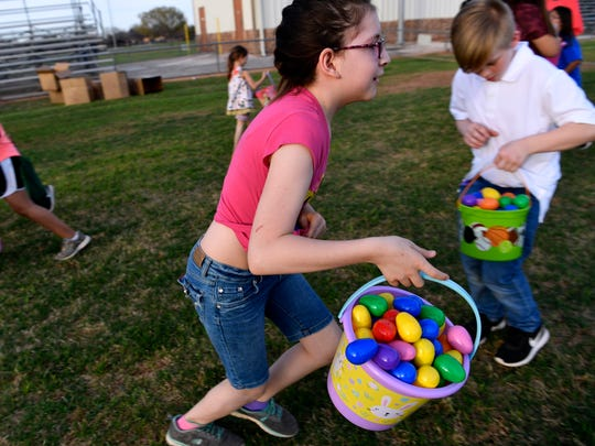 Eggs spill out of buckets and shirts as children run with their Easter eggs during the city of Abilene's annual Evening Easter Egg Hunt at Lee Sports Complex Saturday.