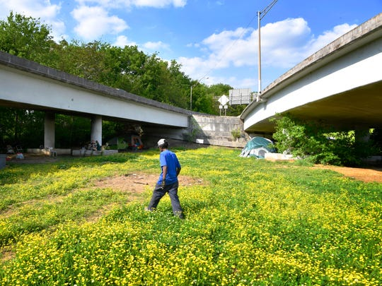 Irving Scott walks though a field of clover in a homeless camp that is situated under overpasses in East Nashville. Metro is planning to close this homeless camps, called Ellington Camp, in East Nashville.  Wednesday May 2, 2018, in Nashville, Tenn.