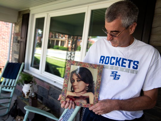 In this file photo from June 14, 2018, Bob Sterner poses for a portrait while holding a photo of his younger sister, Danielle Taylor.