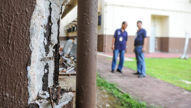 Maintenance workers look at spalling concrete found on an exterior column found at the Z-wing of the Guam Memorial Hospital in Tamuning on Tuesday, July 26. Other areas, including the building's second-floor interior and on the front exterior overhang, the concrete can be seen crumbling away from the structure. Employees working in the affected section, have been moved to other areas of the hospital.