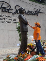 Teresa Olive, of Knoxville, Tenn., touches a statue of Pat Summitt as she pays her respects at the University of Tennessee in Knoxville two weeks ago.