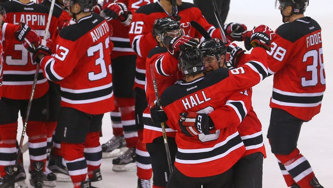 New Jersey Devils left wing Taylor Hall (9) celebrates a win with teammates.