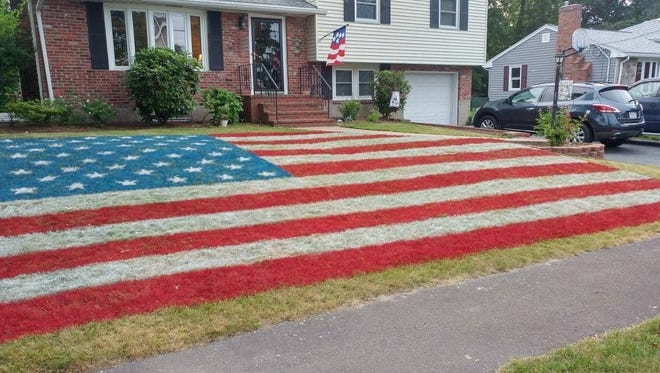 Arthur McCann's tribute to veterans takes up most of thefront lawn of hisNorwood,Massachusetts, home: A giant American flag, spray-painted using field paint.