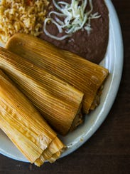 A plate of chicken tamales, wrapped in corn husks,