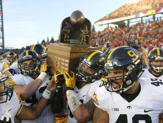 Members of the Iowa Hawkeye football team carry the
